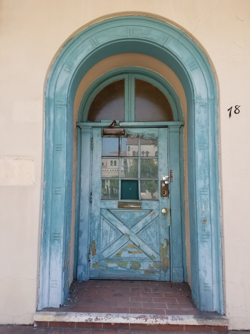 Light aqua arch surrounding an inset wooden door of the same color